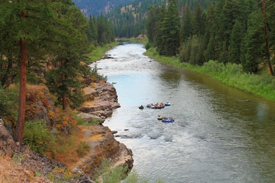 Young man gets ready to jump from a rocky ledge into the Blackfoot River near Sheep Flats to join his buddies floating past.