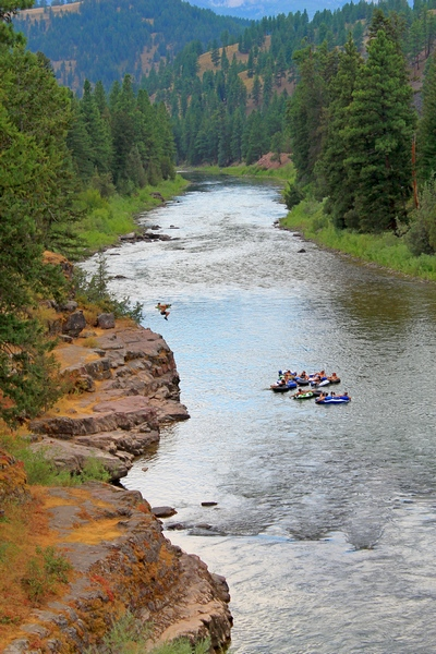 Young man jumps from a rocky ledge into the Blackfoot River near Sheep Flats to join his buddies floating past.