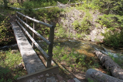 Log foot bridge at Clearwater Lake's out-flowing stream on its northwestern corner.  The stream is the east fork of the Clearwater River.  In the Lolo National Forest north of Seeley Lake Montana.