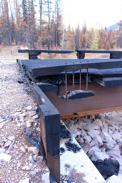 Side view of the burned wooden bridge crossing Morrell Creek on FR 4381 on the way to Morrell Falls trailhead and Pyramid Pass trailhead as it appeared 10/11/17.  The steel substructure may be salvageable.  Morrell Creek below is dry.