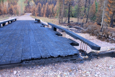 Looking east across the burned wooden bridge crossing Morrell Creek on FR 4381 on the way to Morrell Falls trailhead and Pyramid Pass trailhead as it appeared 10/11/17.  The bridge and forest have sustained heavy damage in the Rice Ridge fire.