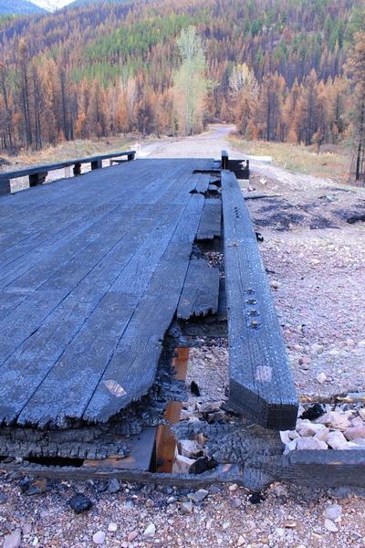 Looking east across the burned wooden bridge crossing Morrell Creek on FR 4381 on the way to Morrell Falls trailhead and Pyramid Pass trailhead as it appeared 10/11/17.  The bridge and forest have sustained heavy damage in the Rice Ridge fire. Morrell Creek below is dry.