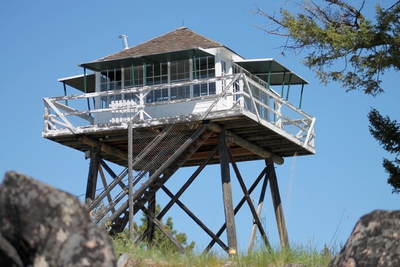Double Arrow Lookout high above, and 2 miles west of  Seeley Lake, MT at an elevation of 4941 feet as seen on 5/23/17. It was built in 1933 and staffed by Forest Service employees until the mid-80s.
