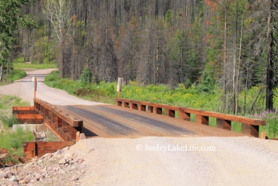 Looking west across the rebuilt wooden bridge crossing Morrell Creek north of Seeley Lake, Montana on FR 4381 near Morrell Falls trailhead and Pyramid Pass trailhead. Date: 7/16/19. This is now open to traffic.